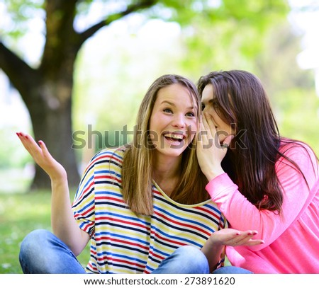 Two girl friends whispering secrets at park