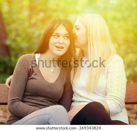 Two girl friends whispering secrets outdoors - stock photo