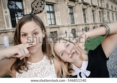 Two girl having fun outdoor, posing in funny costume