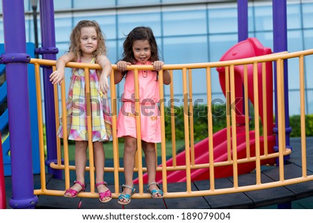 Two girl holding railings on the playground - stock photo