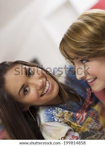 Two Girl lying on bed - stock photo