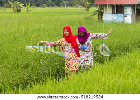 two girl playing bubbles at paddy field
