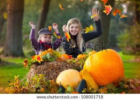 two girl playing in the autumn leaves - stock photo