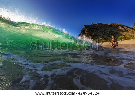 Two girl playing with ocean water. Beautiful semitransparent seascape at sunset time. Big surfing translucent green ocean wave with sun spot. Marine sport water surface.