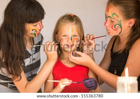 Two girl playing with painting with sister. - stock photo