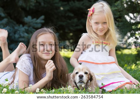 two girl sisters with dog lying on a grass - stock photo
