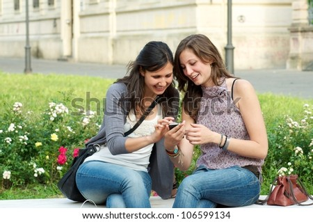 Two Girl While They Make a Speak a Phone - stock photo