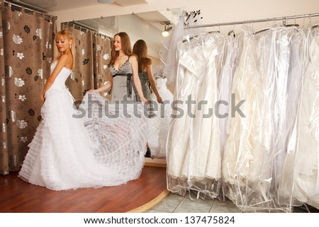 Two girlfriends  - A Bride-To-Be and  bridesmaid  - having fun -Trying On A Wedding Dress - stock photo