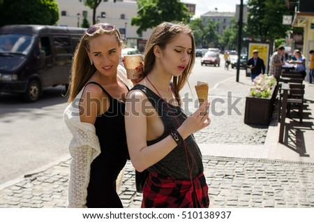Two girlfriends are eating icecream and drinking coffee on the stret