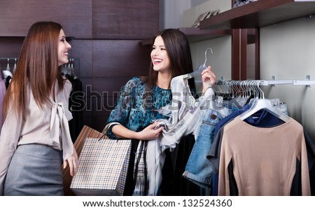 Two girlfriends are joking while do shopping at the store - stock photo