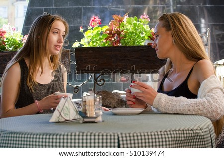 Two girlfriends are sitting in the cafe
