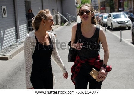 Two girlfriends are walking on the city streets
