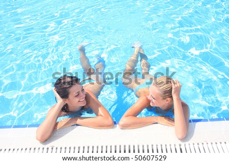 Two girlfriends  enjoying the sun in a swimming pool while  on vacation