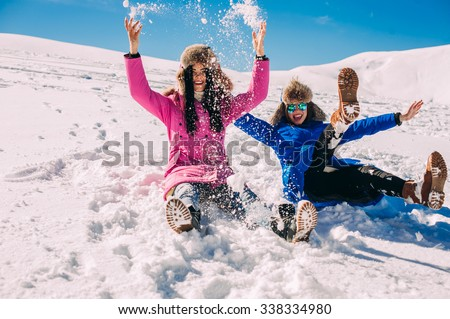 Two girlfriends have fun and enjoy the fresh snow on a beautiful winter day in the mountains - stock photo