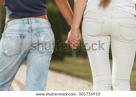Two girlfriends holding hands. Back view. - stock photo