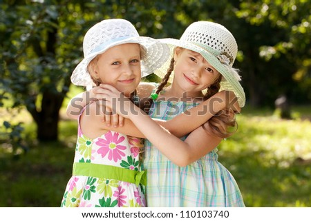 Two girlfriends in a wicker hats and gowns hugging