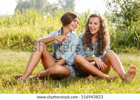 two girlfriends in jeans wear sitting on grass having fun