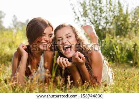 two girlfriends in T-shirts  lying down on grass laughing having good time - stock photo