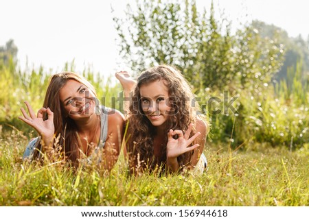 two girlfriends in T-shirts  lying down on grass showing ok sign looking at camera - stock photo