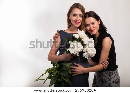 Two girlfriends, one pregnant - stock photo