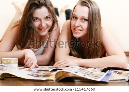 Two girlfriends reading fashion magazines lying on the floor - stock photo