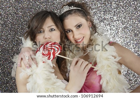 Two girlfriends sharing a feather boa and eating candy on a silver glitter background.