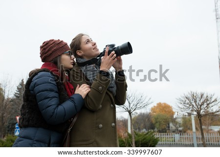 Two girlfriends shooting on the camera in city