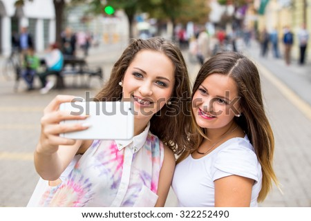 two girlfriends taking selfie photo with mobile phone - stock photo