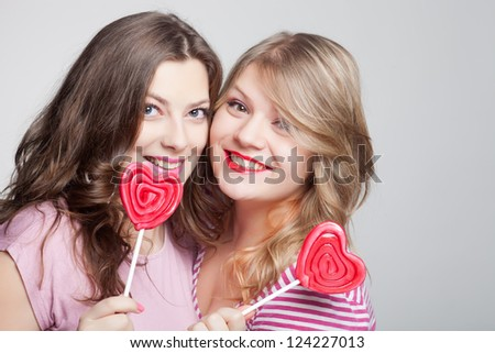 two girlfriends teens with lollipops