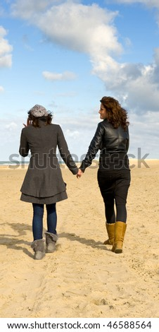 Two girlfriends walking hand in hand on the beach on a beautiful autumn afternoon - stock photo