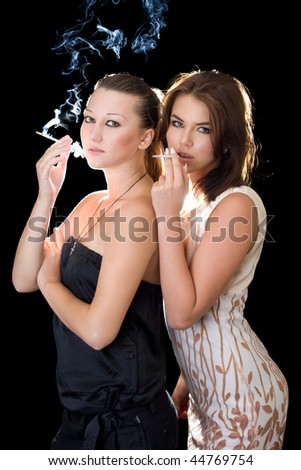 Two girlfriends with cigarettes. Isolated on black - stock photo