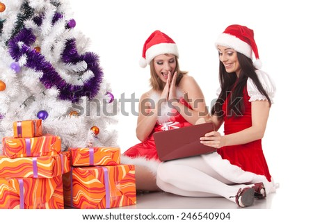 Two girlfriends with laptop and gifts sit near Christmas tree on a white background. - stock photo