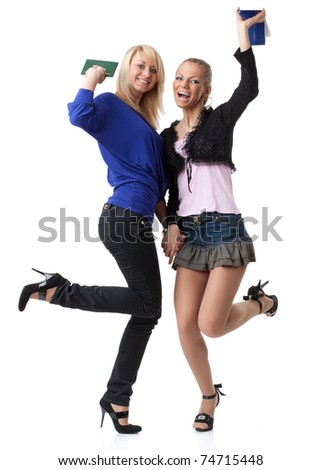 Two girlfriends with the record book on a white background.  Students. - stock photo