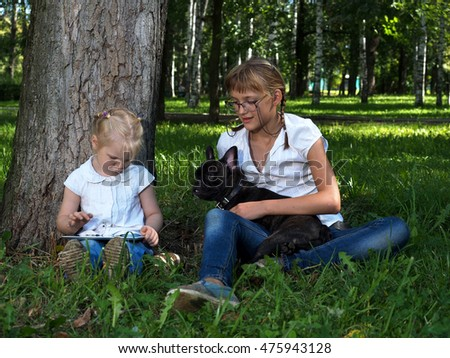 Two girls - adolescent and child sit in the park with tablet computer and dog