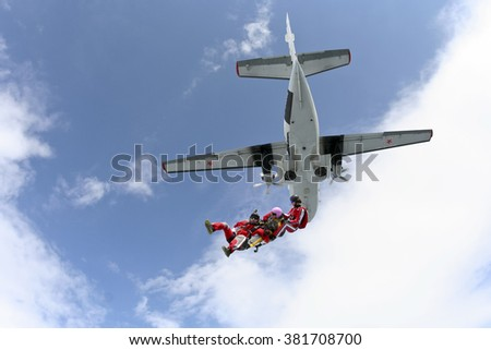 Two girls and a guy skydivers jump out of an airplane.