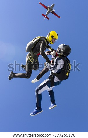 Two girls and a guy skydivers jump out of an airplane. - stock photo