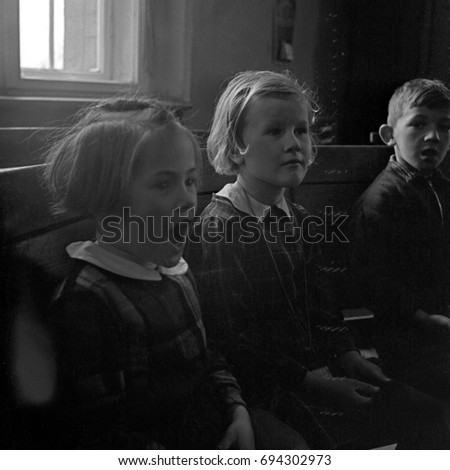 Two girls and boy sitting in classroom