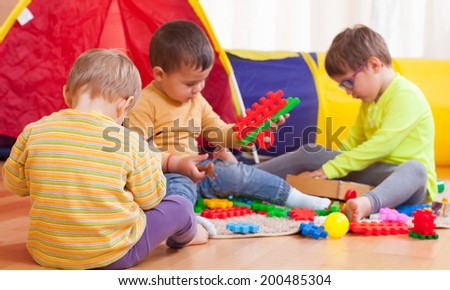 Two girls and boy with toys on  floor at home.  - stock photo