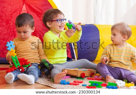 Two girls and boy with toys on  floor at home - stock photo