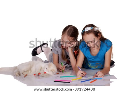 Two girls and cat draw on the album. - stock photo