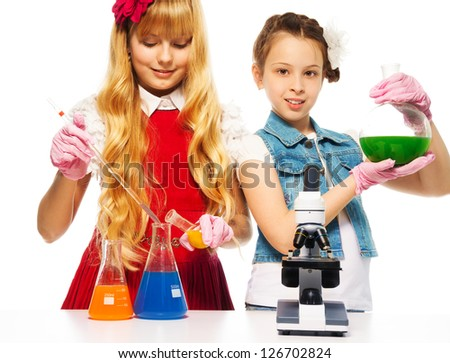 Two girls and chemistry lab equipment - flask and microscope - stock photo