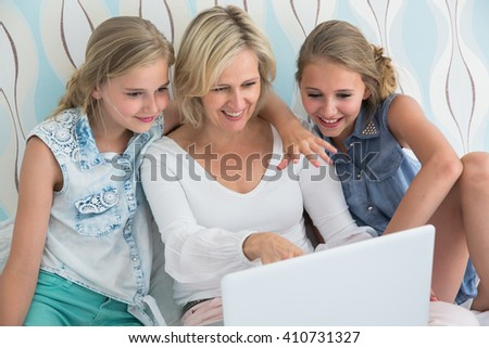 Two girls and mother sitting on the bed with laptop
