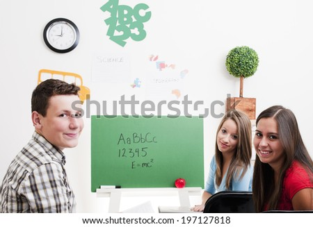 Two girls and one boy sitting in a classroom