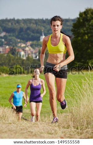 Two girls and one man are running in nature - selective focus - stock photo