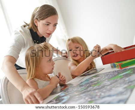 two  girls and teacher playing with table game. A little of DOF. - stock photo