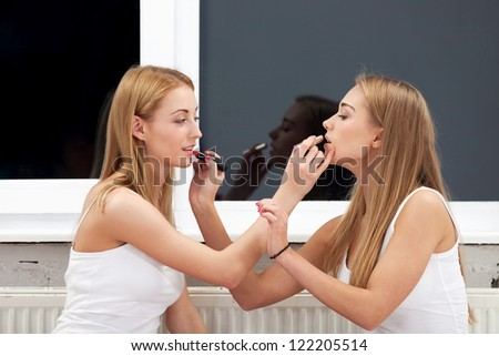 Two girls applying make up to each other - stock photo