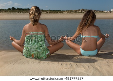 Two girls are doing yoga meditation on the beach
