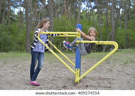 Two girls are playing on the playground on the yellow metal attraction. It's windy. The pine trees are all around. - stock photo