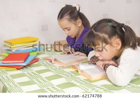 Two girls are reading at the table - stock photo