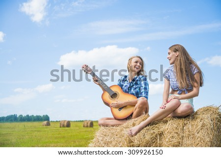 Two girls are sing in full length on straw bale Couple of girlfriends on country vacations are sitting on farm stack of dry thatch Nice hot summer day Young adult woman with slim sexy legs  - stock photo